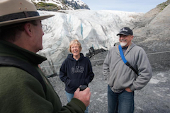 Kenai Fjords ranger and happy visitors in front of a glacier